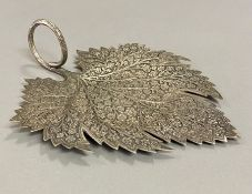 A white metal leaf with intricate design.