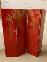 A signed four panel room divider or scren in a Chinese style on red grounds by Andrea Mart (1981)