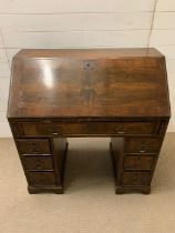 A George III mahogany bureau with sloping fall-front enclosing drawers and pigeonholes, with below 1