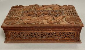 A carved Chinese box with dragon motif.