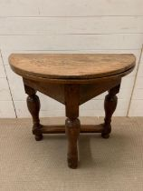 A folding oak side table on turned legs (H76cm W86cm D82cm)