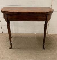 A Victorian card table, decorated with ebonised banding raised turned legs (H73cm W89cm D45cm)