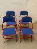 A Set of Four folding Sander metal chairs in red with blue seat pads.