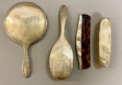 A Four piece silver dressing table set each with a circular cartouche, comprising mirror, hair and