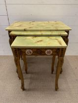 A nest of giltwood tables, inlaid with porcelain mounts and scroll details to side and legs (Largest