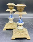 A pair of Delt and brass candlestick holders on square bases and bracket feet