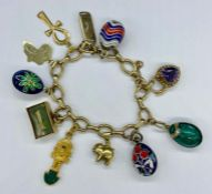 A 9ct gold charm bracelet with a range of charms including four enamel eggs and various hallmarked