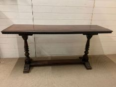 An oak console table on turned supports (H77cm W168cm D50cm)