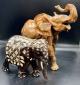 Two decorative elephants one in wood and the other cast metal.