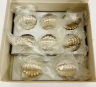 An Eight place setting box of shell themed place setting holders.