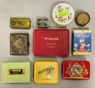 A collection of playing cards along with a cigarette case