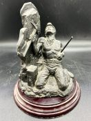 A carved figure of a miner on a stand