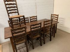 An oak French farmhouse table with eight ladder back high seats (H77cm W210cm D90cm)