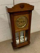 An oak case wall clock with brass face