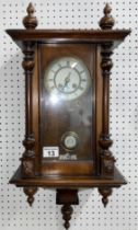 Walnut cased Vienna wall clock with white enamel face with roman numerals, with key