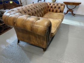An oversized tanned leather chesterfield sofa, on castors, A/F