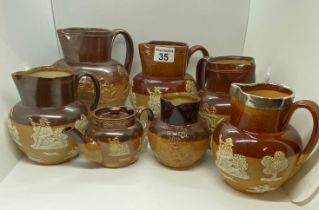 A quantity of Doulton Lambeth ware jugs/pitchers/teapot in various sizes including ; a silver