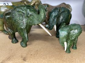 Two hand carved green stone African animals, signed by artists A/F plus three hand carved graduating
