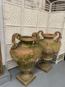 Two oversized Italian terracotta urns with twin handles, relief decorated with swags and lions.