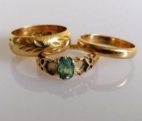 Two gold wedding bands, one with etched decoration and a gem-set ring (two stones missing), all