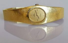 A ladies 18ct yellow gold Omega De Ville wristwatch, the rectangular case enclosing oval champagne