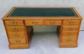 A Georgian-style light oak twin pedestal desk with tooled leather inset over an arrangement of