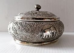 An Indian silver lidded jar with profuse embossed decoration, 7 x 11 cm diameter, with slight dents,