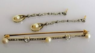 An Art Deco diamond and pearl bar brooch, 70mm. with a pair of near matching earrings, each 50mm,