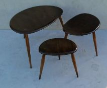 A nest of three Ercol pebble tables and matching coffee table (diam. 74 cm), all with blue labels,