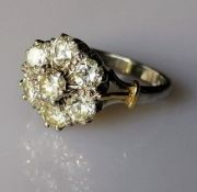 An yellow and white gold flower ring with seven brilliant-cut diamonds, each measuring approximately