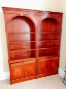 A Sheraton-style mahogany arcaded set of three open bookcases with blind fretwork to cornice and