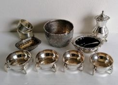 An Art & Crafts set of four circular silver salts with stylised handles by Sibray, Hall & Co Ltd.,