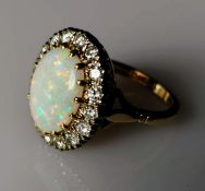 An oval opal cluster ring with sixteen round brilliant-cut diamonds, approximate total weight 1.20