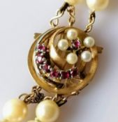 A double rope of cultured pearls with gold and garnet decorated clasp, 56 cm, not marked