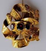 A Victorian gold ribbon-knot brooch with garnet decoration, not marked but tests for high quality