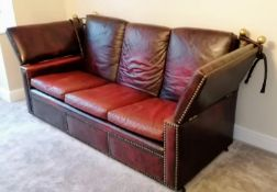 A vintage Knole three-seat drop arm sofa upholstered in red studded leather, 102 h x 230 w x 90 d