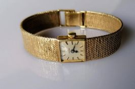A mid-century Omega ladies dress watch with a gold case and bark-effect bracelet strap, in working