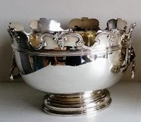 A Victorian silver monteith punch bowl with moulded rim, lion mask handles on a stepped pedestal