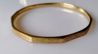 A 9ct yellow gold bangle with faceted decoration, marks rubbed, 12.5g
