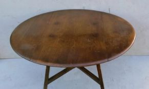 An Ercol beech and elm drop leaf table with X-shape stretcher, blue label, 72 cm H, 113 cm diameter,