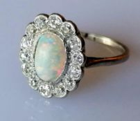 An oval opal (9mm x 6mm) cluster ring with 14 round brilliant-cut diamonds, total approximate