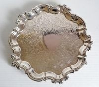 A Victorian silver salver with etched decoration and pie crust border on three claw and ball feet by