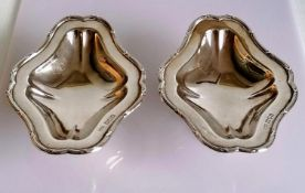 A pair of George V silver tazze with decorated borders, each on a spreading foot by Skinner & Co.,