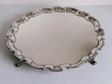 A George II silver salver with pie-crust border on four hoofed feet, initialled to underside, by