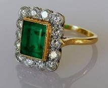 An emerald and diamond cluster ring, milgrain-set in white gold and yellow gold shank: the central