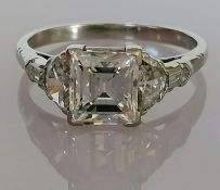 A five-stone diamond ring set with a central modified emerald-cut diamond, flanked by a fancy half-