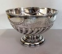 A late Victorian silver punch bowl with embossed swag and half-flute decoration on a stepped foot,