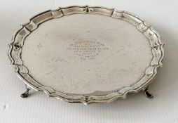 A George V silver salver with pie crust border on four hoof feet by Barker Brothers, Chester,
