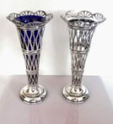 An Edwardian pair of pierced silver vases, one with blue glass liner, each on a stepped base by