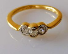A yellow gold three-stone diamond ring with brilliant-cut diamonds, total weight approx. 0.33